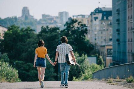 Photo pour Vue arrière de joyeux musiciens de rue à pied et en maintenant les mains dans la ville - image libre de droit