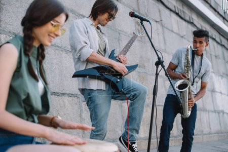 Multiracial young musical band with guitar, drum and saxophone performing on street