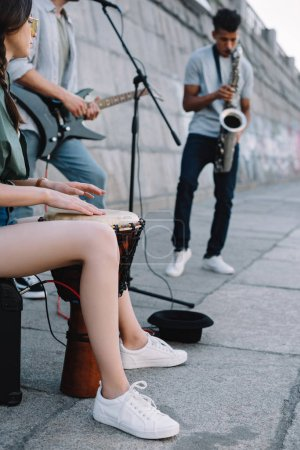 Photo for Talented street musicians with guitar, drum and saxophone performing in city - Royalty Free Image