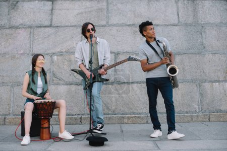Multiracial young people performing in band on street