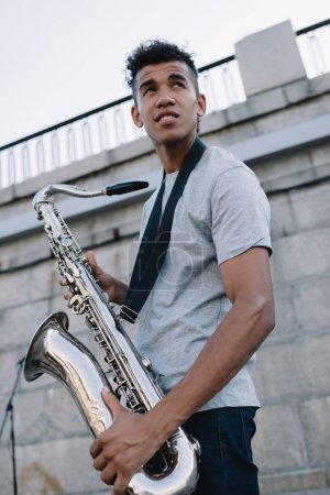 Young and happy african american street musician holding saxophone in city