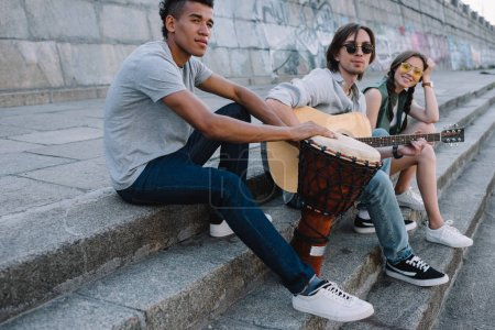 Young and happy multiracial street musicians band sitting with instruments in city