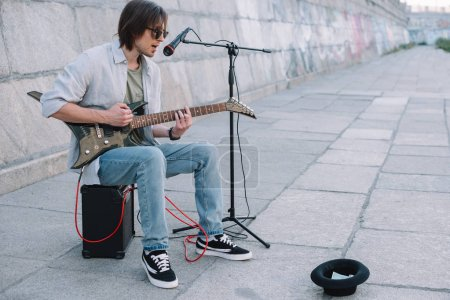 Photo for Young happy busker playing guitar and singing at city street - Royalty Free Image