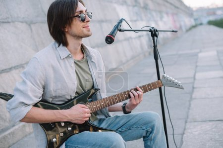 Young man with guitar improvising while performing on street