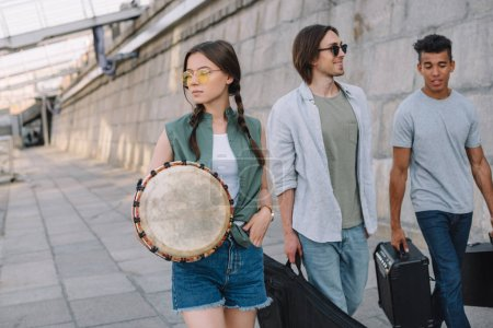 Team of young male and female friends walking and carrying musical instruments in urban environment