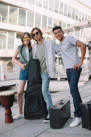 Photo for Multiracial young people posing by musical instruments on street - Royalty Free Image