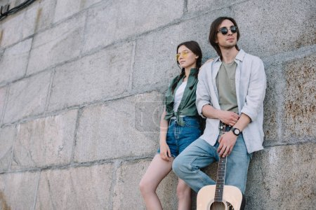 Young girl and man in sunglasses holding guitar by wall on street