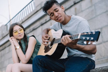 Pretty girl listening to African american man playing guitar in urban environment