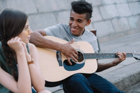 Multiracial young people playing guitar and singing on street