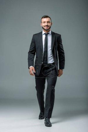 smiling handsome businessman walking on grey