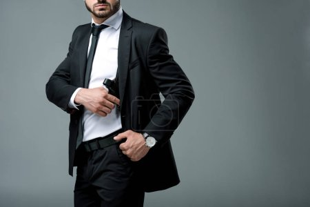 cropped image of security guard in suit taking gun isolated on grey