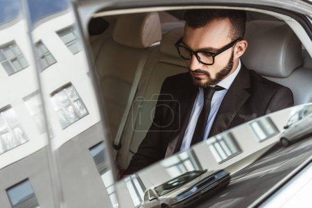 handsome businessman sitting in car and looking down