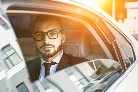 handsome businessman sitting in car and looking at camera during sunset