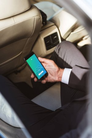 cropped image of businessman holding smartphone with loaded twitter page in car
