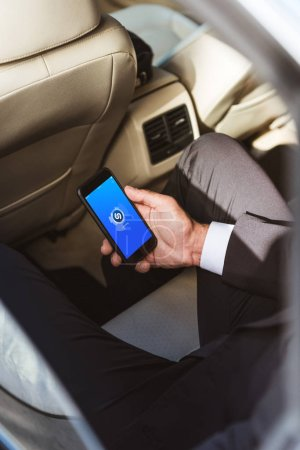 Photo for Cropped image of businessman holding smartphone with loaded Shazam page in car - Royalty Free Image