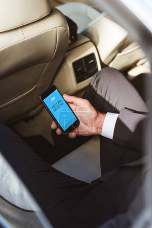 cropped image of businessman holding smartphone with loaded skype page in car