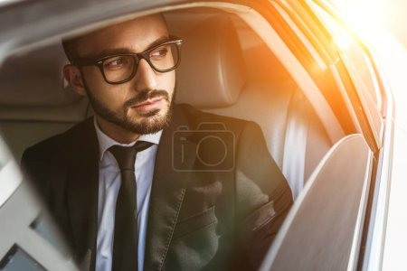 handsome businessman sitting in car and looking away during sunset