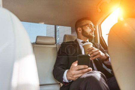 handsome businessman sitting in car with disposable coffee cup and smartphone