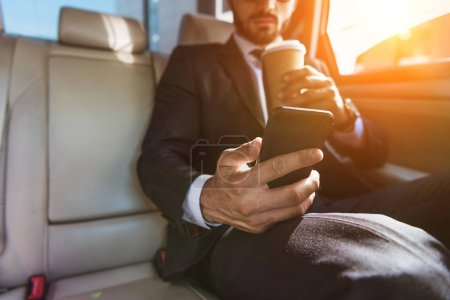 cropped image of businessman sitting in car with disposable coffee cup and using smartphone