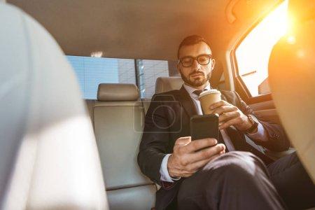 bel homme d'affaires assis dans la voiture avec la tasse à café jetable et à l'aide de smartphone