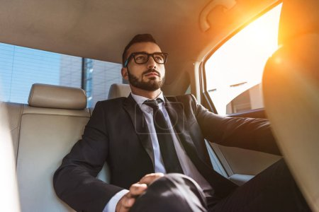 handsome businessman in suit sitting in car during sunset