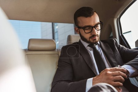 handsome businessman checking time on wristwatch in car