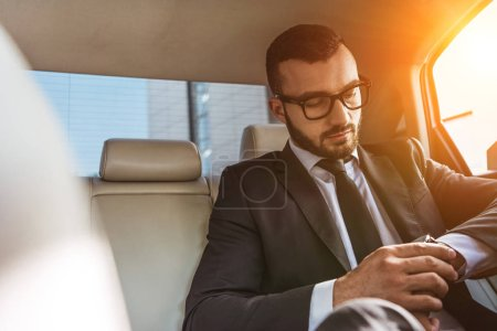 handsome businessman checking time on wristwatch in car during sunset