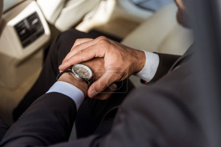 cropped image of businessman checking time on wristwatch in car