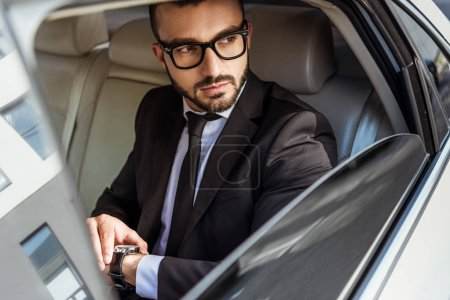 Photo for Handsome businessman checking time on wristwatch in car and looking away - Royalty Free Image