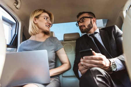 low angle view of handsome businessman and assistant working in car with laptop and smartphone
