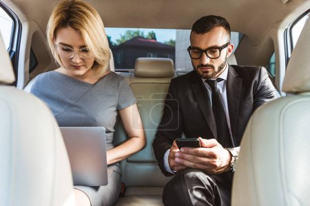 handsome businessman and assistant working in car with laptop and smartphone