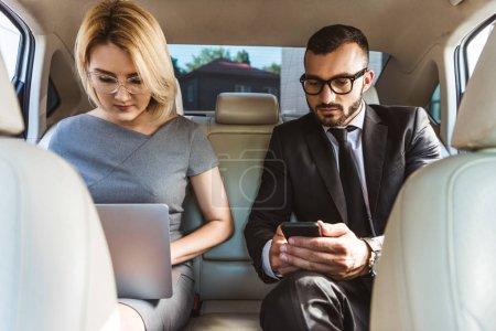 Photo pour Bel homme d'affaires et assistant travaillant en voiture avec ordinateur portable et smartphone - image libre de droit