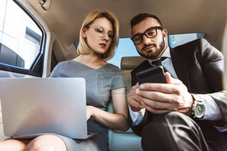 low angle view of handsome businessman showing something on smartphone to assistant in car
