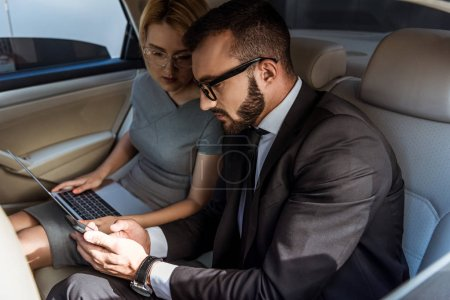 handsome businessman showing something on smartphone to assistant in car