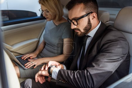 handsome businessman checking time and assistant working with laptop in car