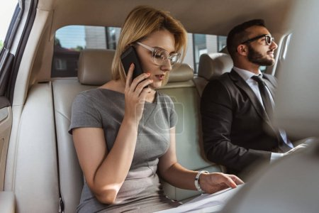attractive businessman assistant talking by smartphone in car