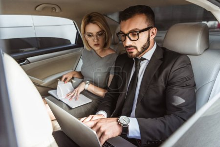 handsome businessman working with laptop in car, secretary sitting with notebook