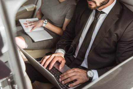 cropped image of businessman working with laptop in car, secretary sitting with notebook