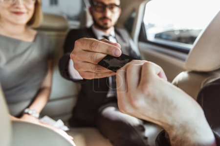 businessman giving credit card to driver to pay for taxi