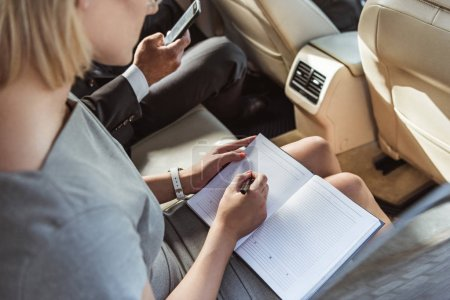 cropped image businessman and assistant working in car with smartphone and notebook