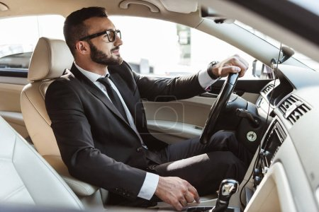 Photo for Side view of handsome driver in suit driving car - Royalty Free Image