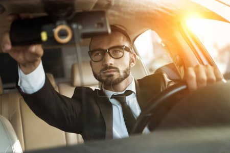 handsome driver in suit driving car and fixing mirror during sunset