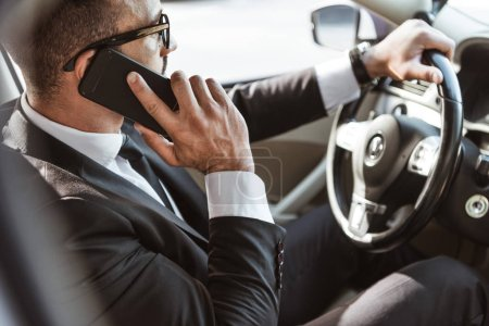 side view of handsome driver in suit driving car and talking by smartphone
