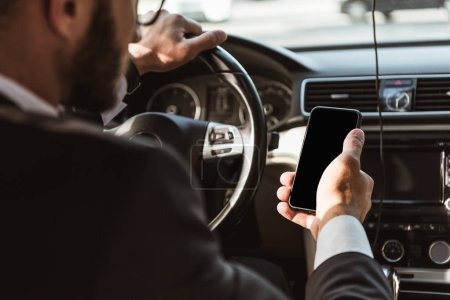 Photo for Cropped image of driver in suit driving car and holding smartphone - Royalty Free Image
