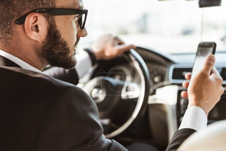 Photo for Handsome driver in suit driving car and holding smartphone - Royalty Free Image