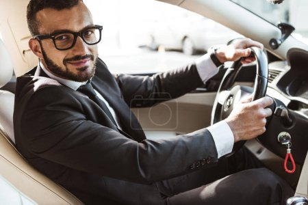 Photo for Side view of handsome driver in suit driving car and looking at camera - Royalty Free Image