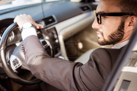 side view of handsome driver in suit and glasses driving car