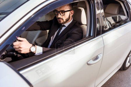 handsome driver in suit and glasses driving car