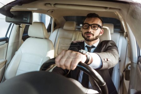 Photo for Cheerful handsome driver in suit and glasses driving car - Royalty Free Image