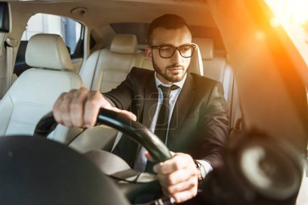 handsome driver in suit and glasses driving auto during sunset